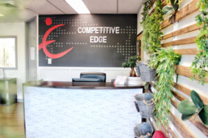 Competitive Edge Waiting Room with front desk, mural and plant wall